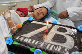 United Nations Population Fund staff gives a cake to the family of newborn baby girl named Danica Camacho, the Philippines' symbolic 'seven billionth baby' who is part of the UN's seven billion global population projection, in Fabella Maternity hospi
