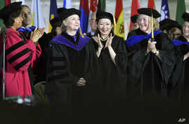 Faculty members cheer former Secretary of State Hillary Clinton after she delivered the commencement address at Wellesley College, May 26, 2017 in Wellesley, Mass. Clinton graduated from the school in 1969.