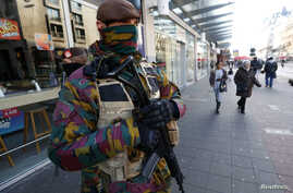 Belgian soldiers patrol in central Brussels as police search area during a continued high level of security following the recent deadly Paris attacks, Belgium, Nov. 23, 2015.