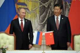 Russia's President Vladimir Putin, and China's President Xi Jinping, right, smile during signing ceremony in Shanghai, China on  May 21, 2014.