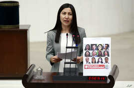 FILE - Leyla Birlik, a lawmaker from pro-Kurdish Peoples' Democratic Party, HDP, speaks next to a placard with photos of 11 jailed HDP lawmakers in Ankara, Turkey, Jan. 19, 2017.