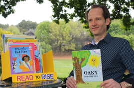 Steve Tsakaris presents one of Read to Rise's unique mini-libraries. (D. Taylor/VOA)