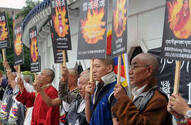 Tibetans display portraits of people who killed themselves in self-immolation, during a protest in front of the Liberty Square in Taipei on October 19, 2011. (AFP)