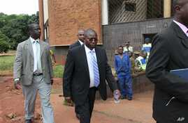 Elton Mangoma, center, Zimbabwe's Minster of Energy and Power Development outside the magistrates courts, accompanied by two unidentified police detectives in Harare, March, 11, 2011