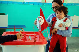 FILE - A woman casts her vote with her child during the first round of the Tunisian presidential election in a polling station at Marsa, outside Tunis, Nov. 23, 2014. The vote was another step forward in Tunisia's peaceful transition to democracy.