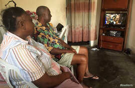 A couple watches the inauguration of incumbent President Ali Bongo Ondimba in Libreville, Gabon, Sept. 27, 2016.