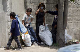Syrian refugee children collect plastics as they stand along a street in south of Sidon, southern Lebanon, June 10, 2014.
