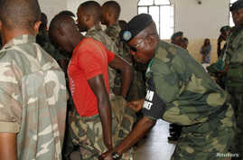 FILE- A Congolese soldier is stripped of his rank and uniform after the mass trial of 39 soldiers inside a military court in Goma in eastern Democratic Republic of the Congo, May 5, 2014. The court martial sentenced the 39 soldiers on counts of rape