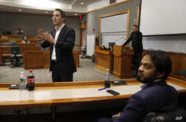 "Lorenzo Vidino, of Milan, Italy, top left, director of the Program on Extremism at George Washington University, addresses an audience during a meeting titled ""Resilience to Violent Extremism: Effective Intervention Approaches,"" at Suffolk Law School..."