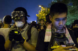 Protesters look their phones as they block the entrance to the offices of Hong Kong's Chief Executive Leung Chun-ying in Hong Kong, Oct. 2, 2014.