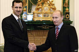 FILE -  In this Tuesday, Dec. 19, 2006 file photo Vladimir Putin, then Russian President, right, and his Syrian counterpart Bashar Assad smile as they shake hands in Moscow's Kremlin