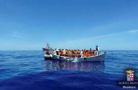 Migrants sit in their boat during a rescue operation by Italian navy ship Grecale (unseen) off the coast of Sicily in this handout picture from the Italian Marina Militare, released May 6, 2016. Italy's coast guard has rescued about 1,000 people off