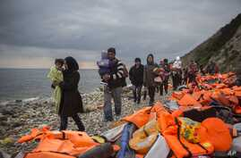 Refugees and migrants walk along a beach after crossing a part of the Aegean on a dinghy, from Turkey to the Greek island of Lesbos, Dec. 12, 2015.