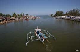 FILE - In this May 7, 2013 photo, a fishing boat returns to their village in the coastal town of Masinloc, Zambales province, northwestern Philippines.