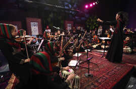 In this Feb. 15, 2017, photo, orchestra leader Zarifa Adiba, 18, conducts during a concert in Kabul. Afghanistan's first all-female symphony is trying to change attitudes in a deeply conservative country where many see music as immoral, especially fo
