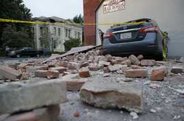 Bricks and fallen rubble cover a car with the old courthouse in the background following an earthquake in Napa, California, Aug. 24, 2014.