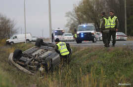 A Surete du Quebec officer investigates an overturned vehicle in Saint-Jean-sur-Richelieu, Quebec, Oct. 20, 2014. Two Canadian soldiers were injured, and one died, in a hit-and-run Monday by a male driver who later was shot by police officers.