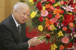 Then Cambodian King Norodom Sihanouk stands beside flowers given by the Chinese government during a meeting with Chinese State Councilor Dai Bingguo (not seen) in Beijing, October 30, 2006.