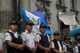 FILE - People protest against a decision by Guatemala's President Jimmy Morales to shut down the United Nations International Commission Against Impunity, CICIG, at Constitution Square in Guatemala City, Sept. 1, 2018.