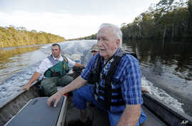 William Larymore, left, of the South Carolina Department of Natural Resources, and Salvatore Cirencione, of the State Law Enforcement Division, partially visible behind, help resident Franklin Bessemer, who lives on the river, back to a pier on the W