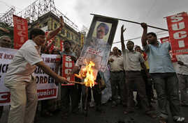 Activists of Socialist Unity Center of India (SUCI) burn an effigy with a portrait of Indian Prime Minister Manmohan Singh during a protest in Kolkata, India, September 15, 2012.