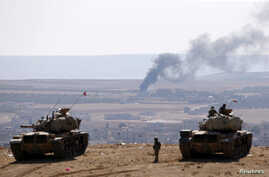Turkish army tanks are seen on the Turkish side of the border as smoke rises from the Syrian town of Kobani Oct. 8, 2014.