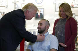 President Donald Trump awards a Purple Heart to U.S. Army Sgt. 1st Class Alvaro Barrientos, with his wife, Tammy Barrientos, right, at Walter Reed National Military Medical Center, in Bethesda, Md., April 22, 2017.