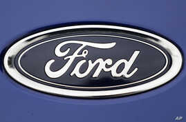 FILE  - In this Aug. 22, 2017 file photo, a Ford emblem is seen on a car at a store in London.