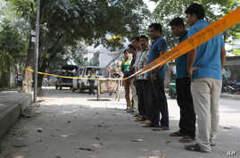 Bangladeshi police and detectives stand by the site where Italian citizen Cesare Tavella was gunned down by unidentified assailants in Dhaka, Sept. 29, 2015.