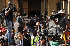 Olympic and Paralympic track star Oscar Pistorius (bottom L) leaves the North Gauteng High Court in Pretoria, October 14, 2014. The 27-year-old Paralympic and Olympic athlete, whose lower legs were amputated as a baby, was convicted of culpable homic