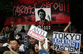 Protesters holding placards shout slogans at a rally against Japan's Prime Minister Shinzo Abe's push to expand Japan's military role in front of Abe's official residence in Tokyo, June 30, 2014.
