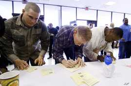 FILE - Job seekers fill out their forms at an employment expo in Jackson, Miss., March 17, 2009.