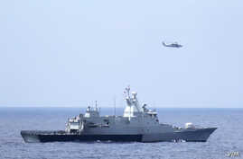 The Royal Malaysian Navy corvette KD Terengganu (FSGHM 174) and a U.S. Navy MH-60R Sea Hawk helicopter from the Blue Hawks of Helicopter Maritime Strike Squadron (HSM) 78, Det. 2, from the guided-missile destroyer USS Pinckney (DDG 91), conduct a coo