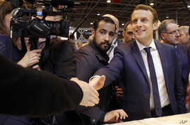 FILE -  Centrist presidential candidate Emmanuel Macron (C) is flanked by his bodyguard, Alexandre Benalla (L) while visiting the Agriculture Fair in Paris, March 1, 2017.