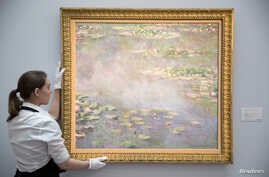 A gallery assistant poses with the painting Nympheas by Claude Monet at a photo-call for Impressionist and Modern Art Evening Sale at Sotheby's auction house in London, June 18, 2014.