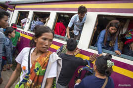 Cambodian workers get off a train as they prepare to migrate back to Cambodia at Aranyaprathet train station in Sa Kaew June 15, 2014.