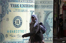 An Egyptian walks in front of a closed currency exchange office as banks, schools and the stock market remained closed for the second working day in Cairo, Egypt, January 31, 2011