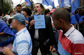 """An opposition supporter holds a placard that reads """"No to the violation of the constitution"""" during a gathering to demand a referendum to remove Venezuela's President Nicolas Maduro in Caracas, Venezuela, Sept. 7, 2016."""