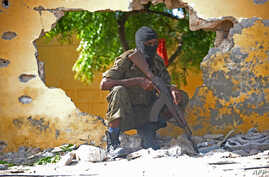 FILE - A Somali soldier stands guard next to the site where al-Shabab militants carried out a suicide attack against a military intelligence base in Mogadishu, June 21, 2015.