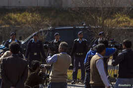 A car carrying former Pakistani President Pervez Musharraf, drives past members of the media as he leaves the special court formed to try him for treason in Islamabad Feb. 18, 2014.