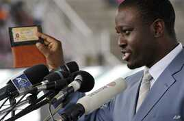 Prime Minister of Ivory Coast  Guillaume Soro displays his identity card as he speaks during a rally at a stadium in Bouake on 3 Oct 2010