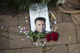 A rose lays next to an image of Muhammad Ali at a makeshift memorial at the Muhammad Ali Center, June 5, 2016, in Louisville, Ky. Ali, the heavyweight champion whose fast fists and irrepressible personality transcended sports and captivated the world