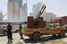 FILE - Members of forces loyal to Libya's eastern government stand near to the Libyan cement factory after the army took control of the factory following clashes with the Shura Council of Libyan Revolutionaries, an alliance of former anti-Gaddafi reb