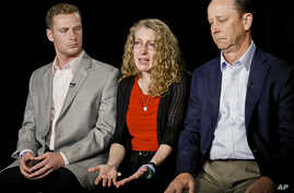 FILE - Evelyn Piazza, center, seated with her husband Jim, right, and son Michael, speaks during an interview May 15, 2017, in New York. The Piazzas talked about Tim Piazza, 19, a brother, son and Penn State sophomore who died in February after he wa