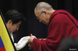 Tibetan spiritual leader the Dalai Lama gives a Tibetan shawl to Japan's main opposition Liberal Democratic Party president Shinzo Abe, at the upper house members' office building in Tokyo, November 13, 2012.