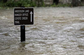 A sign is submerged in the water from Coyote Creek Tuesday, Feb. 21, 2017, in Morgan Hill, Calif. Rains have saturated once-drought stricken California but have created chaos for residents hit hard by the storms.