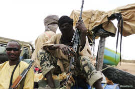 Militiaman from the Ansar Dine Islamic group sit on a vehicle in Gao in northeastern Mali, June 18, 2012. The U.N. Security Council on Monday declared its readiness to consider backing West African military intervention in Mali, where rebels and Isla