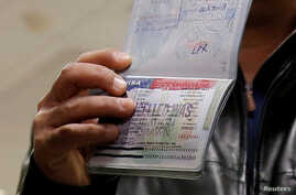 FILE - A Yemeni national who was denied entry into the U.S. shows a cancelled visa in his passport, at Washington Dulles International Airport, in Dulles, Virginia, Feb. 6, 2017.