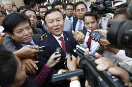 file - Cambodia's main opposition Cambodia National Rescue Party Deputy President and National Assembly Deputy President Kem Sokha, center, speaks to reporters outside the Phnom Penh Municipality Court in Phnom Penh, Cambodia, Wednesday, April 8, 201