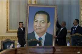 Officials remove a portrait  of ousted Egyptian President Hosni Mubarak at the main Cabinet building in Cairo, February 13, 2011